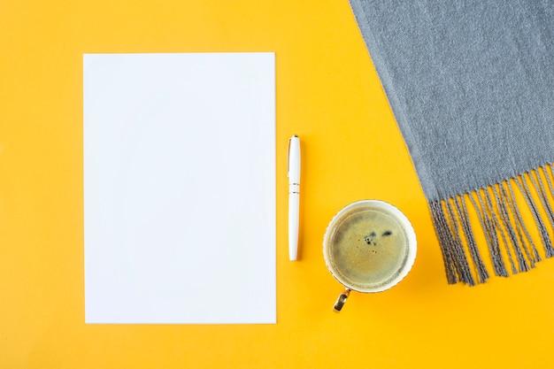 モックアップ - 一杯のコーヒーと秋のスカーフの横にある白い紙。