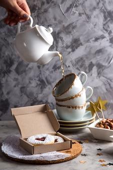 Круглое печенье с джемом в форме сердца в подарочной коробке среди елочных игрушек и звезд на сером фоне