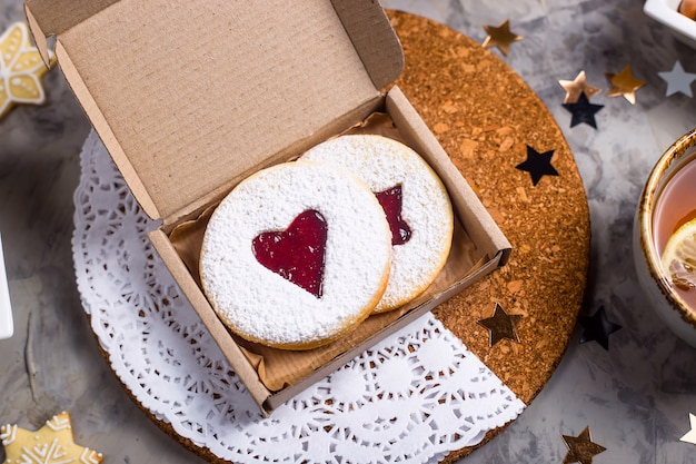 クリスマスの装飾の中でギフトボックスにハート型のジャムとラウンドクッキー