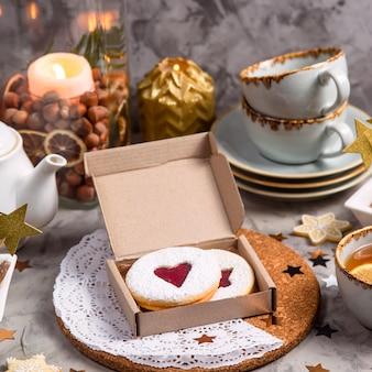 Круглое печенье с джемом в форме сердца в подарочной коробке среди елочных игрушек и свечей на сером столе