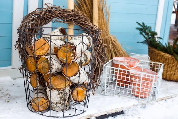 青い国の家の壁で園芸工具の横にある白樺の木の枝編み細工品バスケット