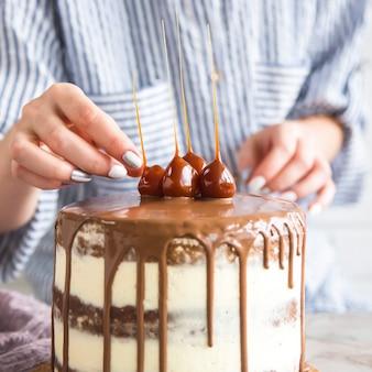 菓子屋が既製のケーキを飾っている
