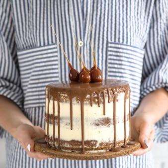Женщина держит маленький круглый красивый торт с шоколадом