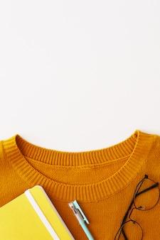 ノート、ペン、メガネをかけた鮮やかな黄色のセーターの襟