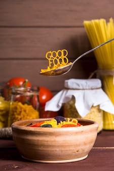 おいしい食べ物は皿の近くのスプーンにパスタが並んでいます