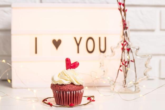 私はあなたを愛して赤いカップケーキの横にある装飾的なランプに書かれて