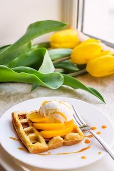 黄色のチューリップの横にある美しいお祝いベルギーワッフル朝食