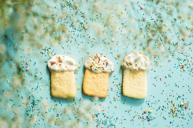ジプソフィラの花の中で青色の背景にイースターケーキの形のクッキー