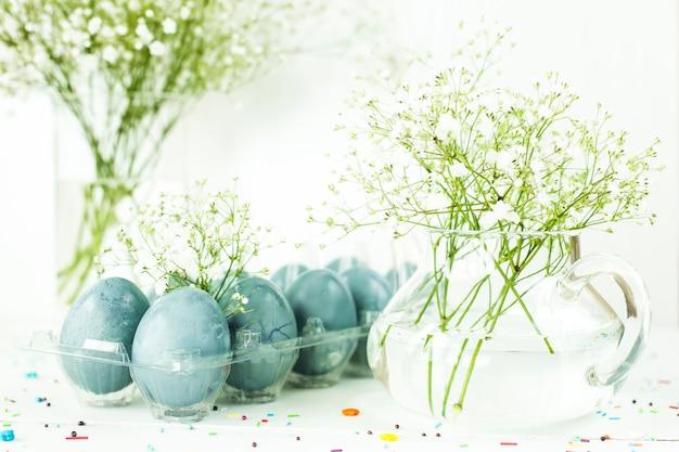 石膏の花束の中で白いテーブルの上の青いイースターエッグ
