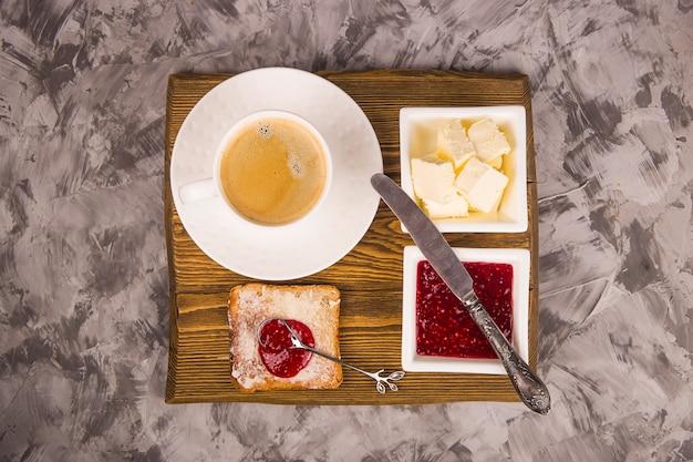Простой завтрак из традиционных продуктов - тост с маслом и малиновым вареньем