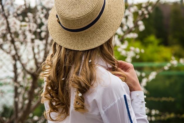 花の中で春の美しいライフスタイルブロンドの女の子