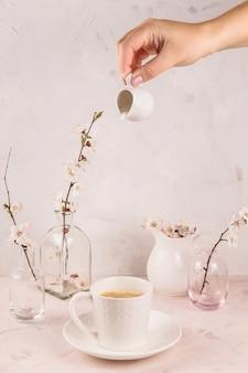 コーヒーを注いでクリームの動きと穏やかな光のミニマルな静物