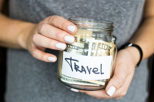 女性がドルでいっぱいの旅行のために貯金を持っています。ファイナンスの概念の蓄積