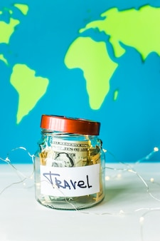 明るい世界地図の背景にドルとガーランドの旅行のための貯金箱。旅行のためのお金。蓄積の概念