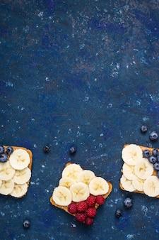 ピーナッツバター、バナナ、ラズベリー、ブルーベリーのベジタリアンランチサンドイッチ