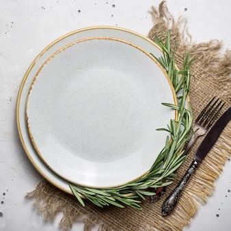 Пустая деревенская тарелка с мешковиной салфеткой и столовыми приборами