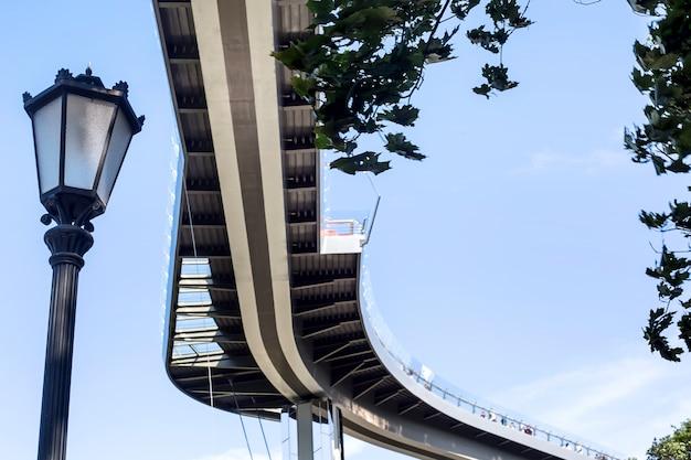 空を背景に湾曲した現代都市建築橋