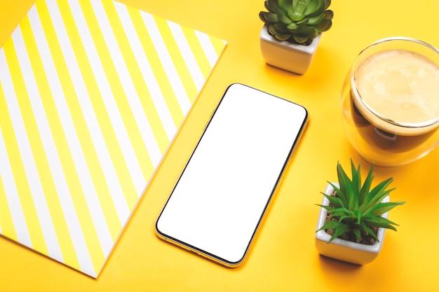 黄色のデスクトップ上の近代的な電話画面。