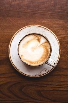 白いカップに芸術と美しいカプチーノ。トップビュー、クローズアップ。