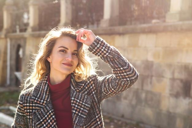 日光の下で秋のコートに金髪のウェーブのかかった髪と美しいモダンな女の子の肖像画。
