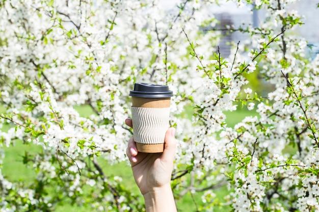 Женская рука держит одноразовую чашку кофе на фоне цветущего весеннего дерева.