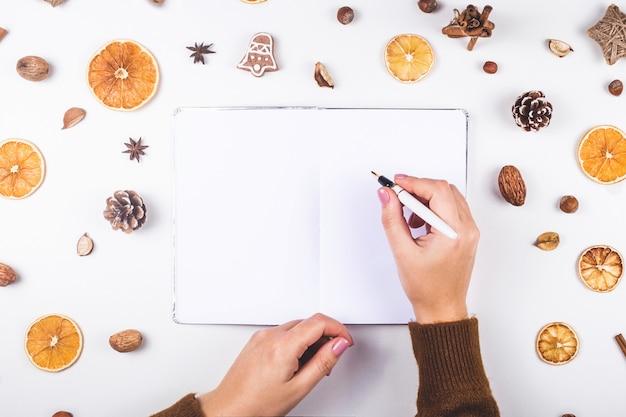 乾燥オレンジとコーンの間でノートに書く婦人。