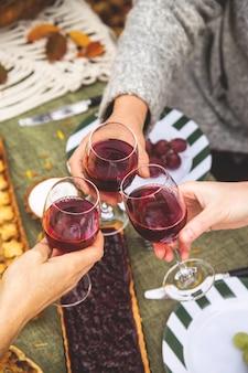 女性は秋の家族の夕食でワインとグラスをチャリンという音します。