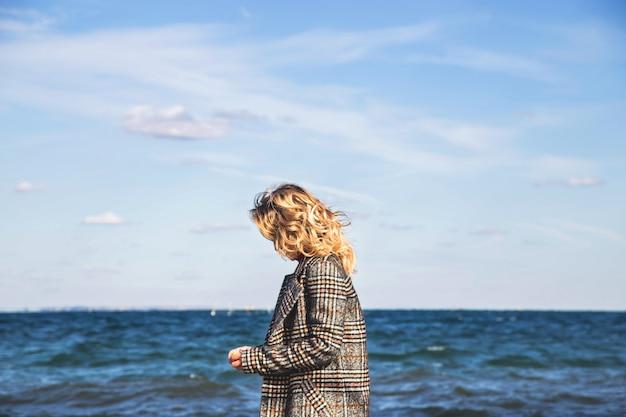 Красивая девушка гуляет осенью и практикует осознанность у моря.