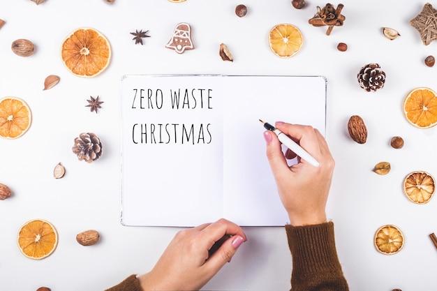 乾燥したオレンジとコーンの間でノートにゼロクリスマス廃棄物を書いた女性。