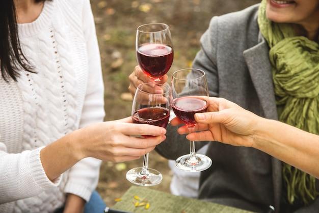 Женщины чокаются бокалами с вином на осеннем семейном ужине.