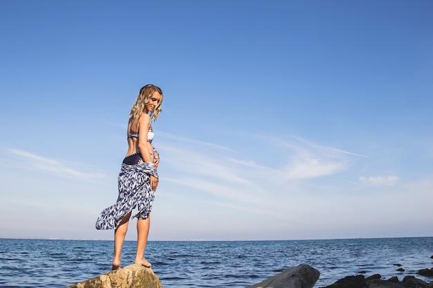 海を旅する白人の女の子が水着姿で海岸に立っており、自然を楽しんでいます。