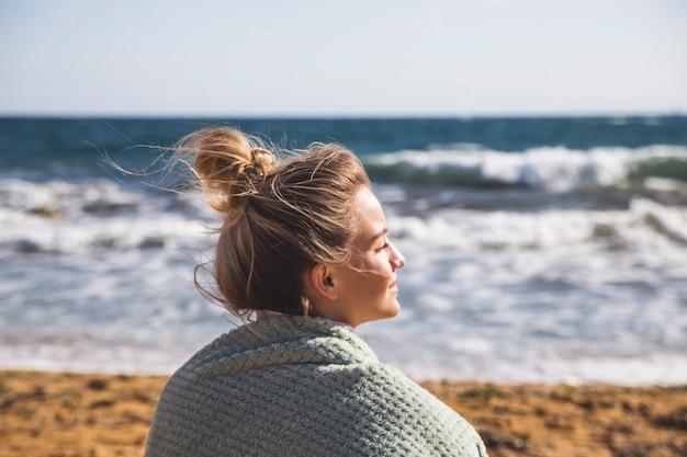 白人の女の子が海のそばの砂の上に座って、目を閉じて自然への旅行を楽しんでいます。