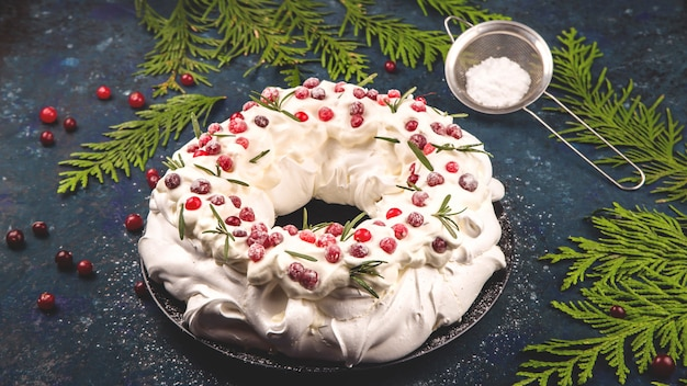 Рождественский десерт павлова безе со взбитыми сливками, украшенный клюквой и розмарином.