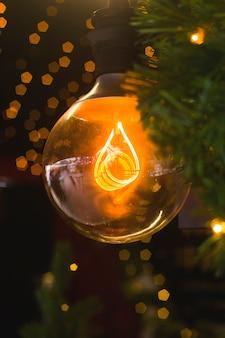 Желтая лампа среди ветвей елки и рождественские огни.