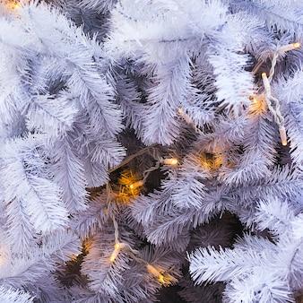 Белые еловые ветки искусственной елки с желтыми огнями. фон и копия пространства.
