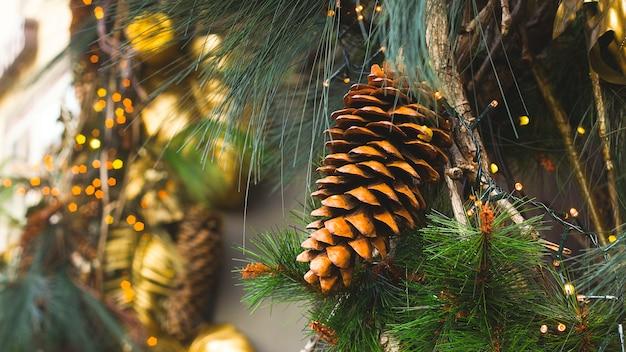 Современное роскошное украшение для дерева с золотыми листьями и натуральными шишками.