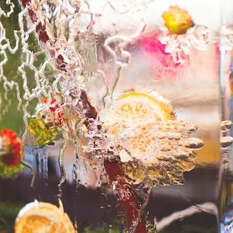 Большой кусок льда с узорами и замороженным лимоном и корицей внутри.