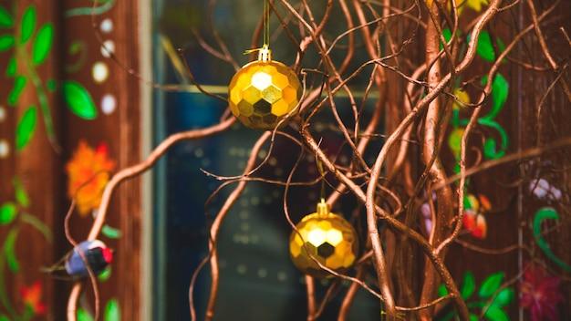 Современное новогоднее украшение с золотыми шарами и натуральными ветками вместо елки.