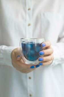 古典的な青のマニキュアを持つ女性は、抹茶ブルーティーのガラスを保持しています