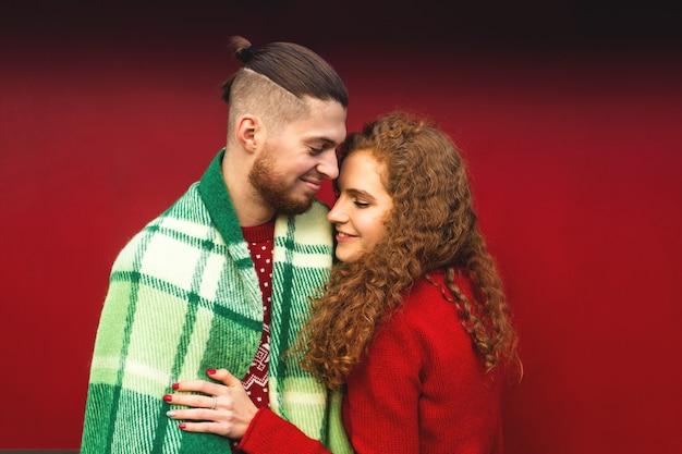 Влюбленные обнимаются и радостно улыбаются в уютной рождественской атмосфере.
