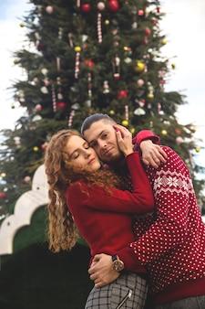 赤いセーターを着た男と少女は、クリスマスツリーに喜んで笑っています。