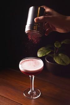 Ягодный красный коктейль с пеной в стакане на темном столе