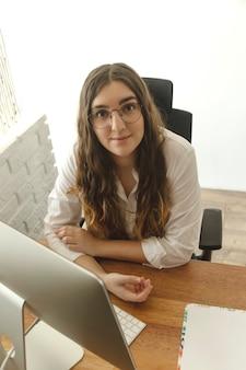 コンピューターを使用してテーブルに座っている女性。ホームオフィスのコンセプトです。
