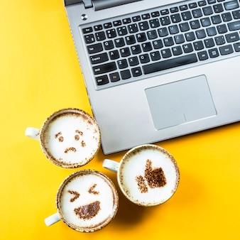 Улыбка смайликов нарисована на чашечках капучино рядом с ноутбуком на желтом фоне