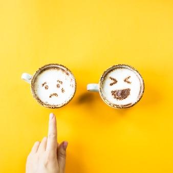 Смех и печаль эмодзи нарисованы на чашках для капучино на желтом фоне