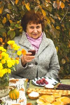 幸せな高齢者の女性は、お祝いテーブルでワインを飲みます。