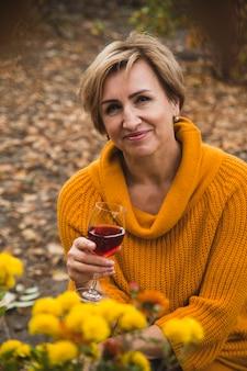 成熟した女性がワインを飲み、カメラを見ながら笑っています。