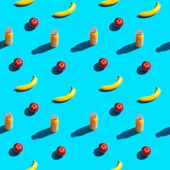 明るい黄色のバナナ、赤いリンゴ、青い背景にジュースのボトル。シームレスパターン。