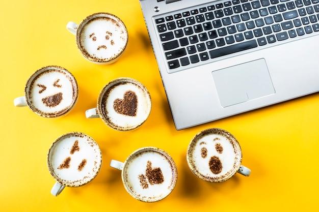 ノートパソコンの横にあるカプチーノのカップに描かれた笑顔の絵文字