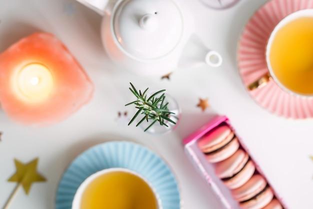 緑茶、星と小さな花瓶のビンテージカップの間でピンクのマカロン付きギフトボックス